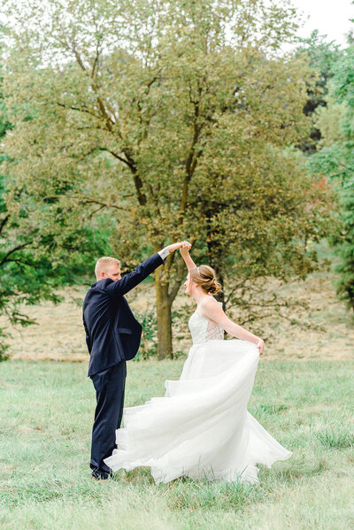 groom twirls his bride at pioneers park