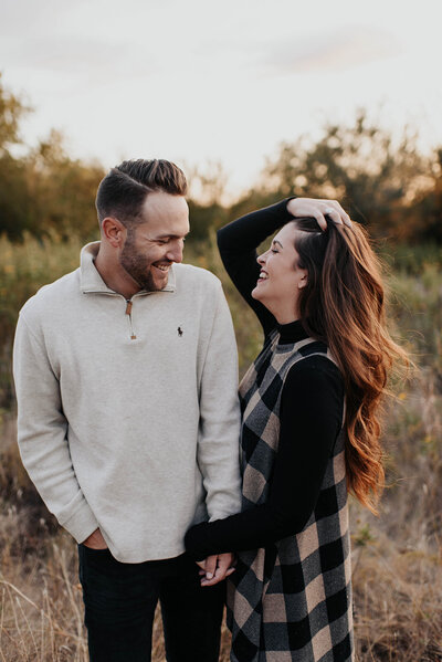 Couple laughing together holding hands during their engagement session