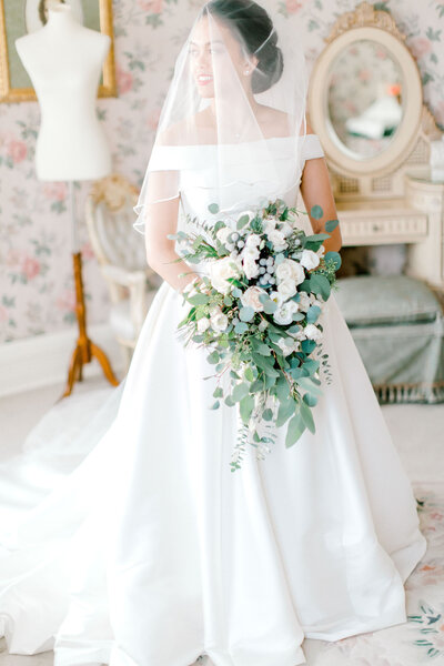 bride standing in the middle of getting ready room holding flowers