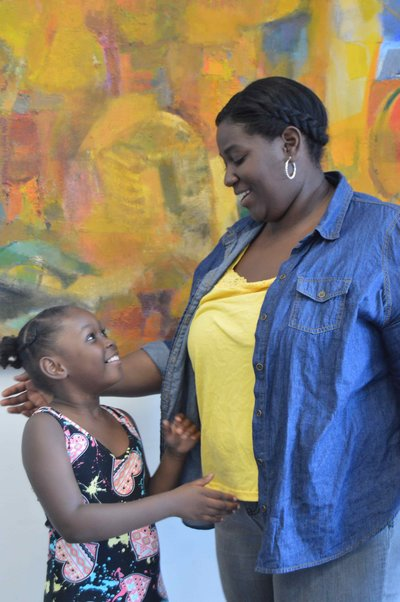 african american woman in a denim shirt holding her younger daughter