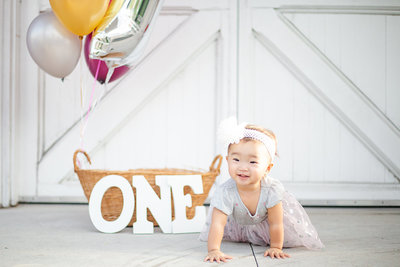 A one year old girl crawls in front of birthday decorations in Wauchula, Florida.