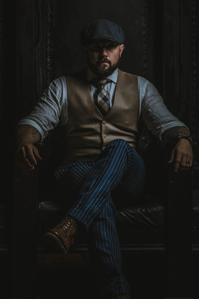 Male photographer sitting on throne in vintage suit similar to peaky blinders