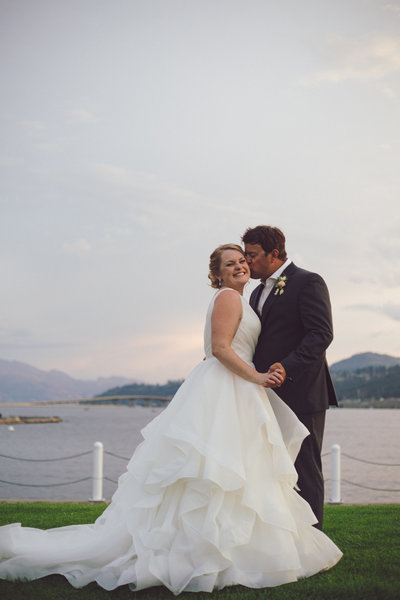 Newly weds kissing cheeks on the boardwalk in downtown Kelowna at the Delta Grand