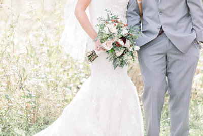 Bride and groom in a field showing off bouquet