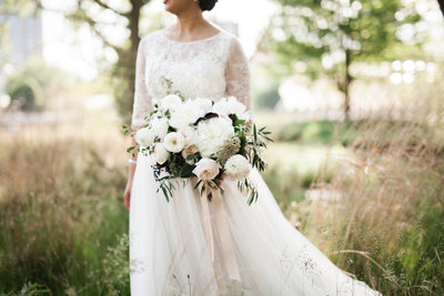Bride with garden style bouquet in field.