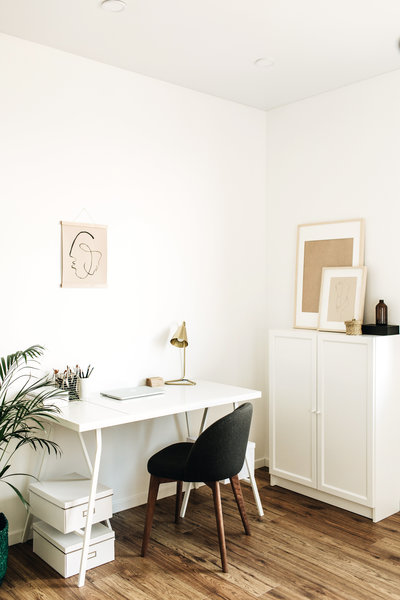 office with white desk and gold lamp with plant