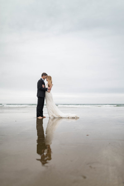 Maine wedding couple on beach with reflection on water