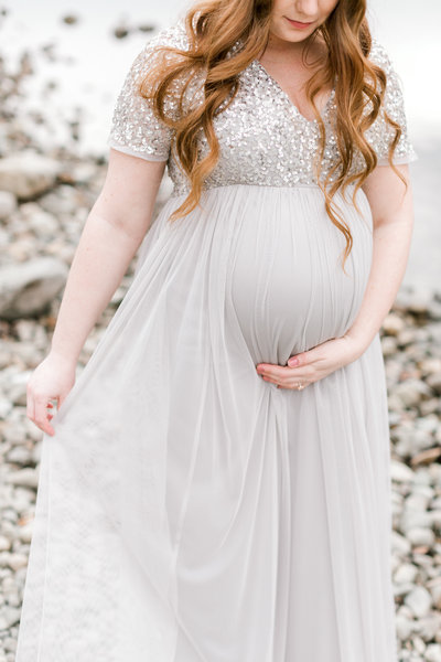 Pregnant woman in flowy dress holding belly standing by lake