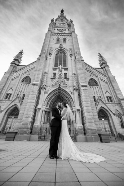 A dramatic black and white wedding photo in front of a church.