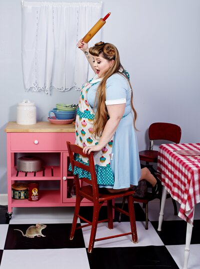 woman in a  light blue pinup dress in Boudoir and pinup by Janet Lynn's pinup Kitchen posing for a pinup photo.