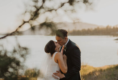 bride and groom kissing by the water