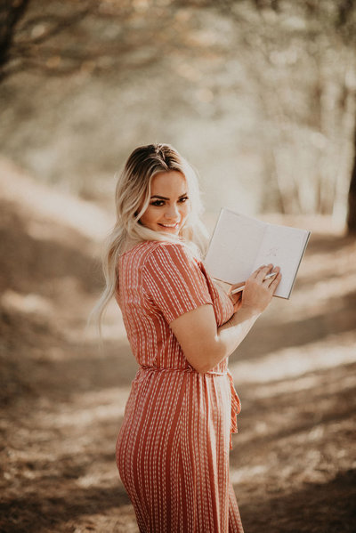 woman holding book while smiling