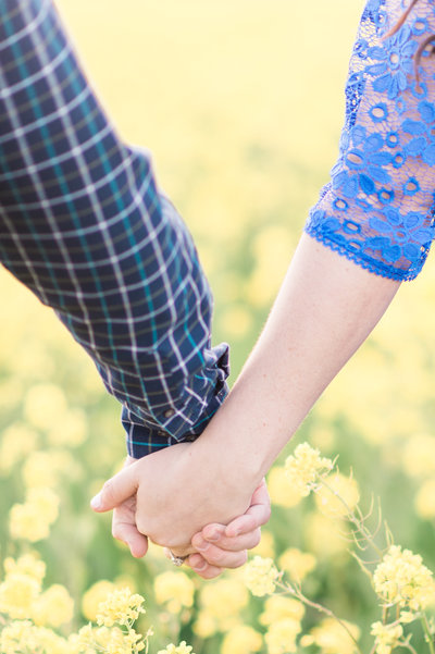 Couple holding hands in a bright field of flowers.