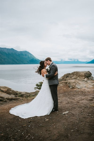 wedding couple hugging on rocky cliff in Hope Alaska after their wedding