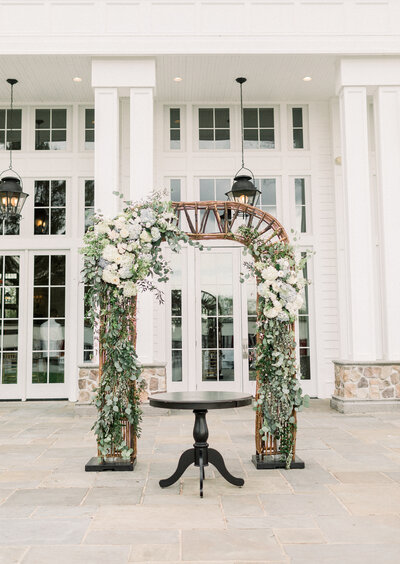 arbor with white flowers and table
