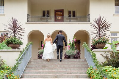 Groom holds his brides dress train as they walk up the steps at Elsie Perrin Williams Estate