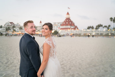 Bride and Groom walking on the beach in front of Hotel Del Coronado