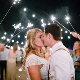 Tahoe Wedding Planners couple kissing under sparkler arch at private Incline wedding venue on Lake Tahoe, Joy of Life Events image by Elena​ Graham Photography
