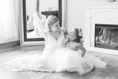 Bride sits on floor in wedding gown with her flower girl