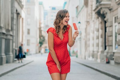 Woman with Red dress eating a red popsicle