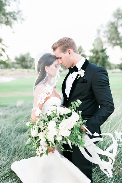 photo of a bride in a lace veil with a white floral bouquet and  a groom in his black tux and bowtie on a grass lawn at Las Vegas Country Club