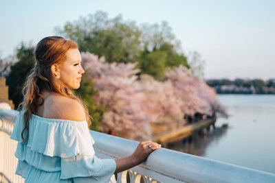 teenage girl looking out onto the  Potaomac river  with flowering trees in the background
