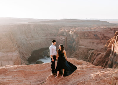 man and woman standing on cliff with canyon in the background