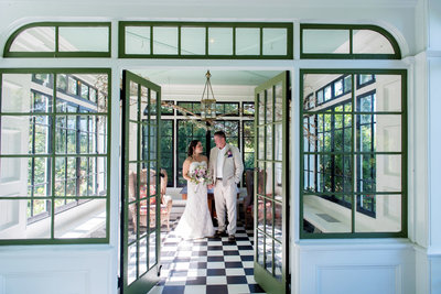 a bride and groom stand in the sunroom at deepwood museum after their wedding