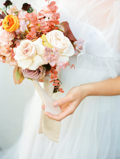 Gorgeous bride's bouquet with peach, oranges and red flowers