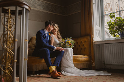 Bride and Groom seated on a yellow sofa by a window at Avington Park