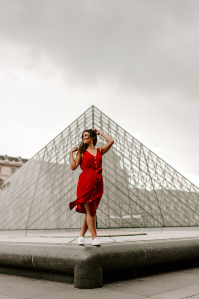 woman wearing red dress and standing in front of piece of art