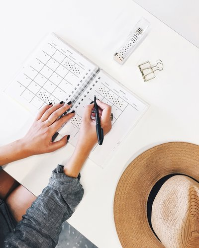 Writing in planner with straw hat