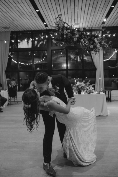 Black and white First Dance photo with the groom dipping his bride