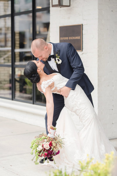 Groom dips his bride romantically on their wedding day outside the Oxford Exchange