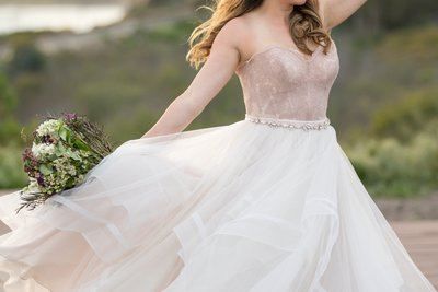 Beautiful bride in white and rose wedding dress on the beach in Santa Barbara, California