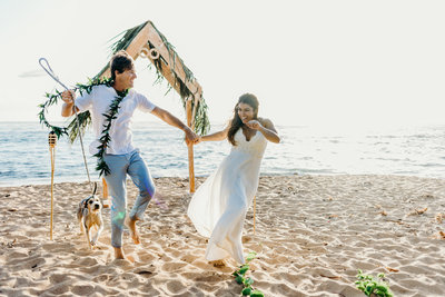 bride & groom running on beach