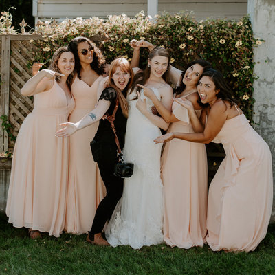 photographer standing with bride and bridesmaids while laughing