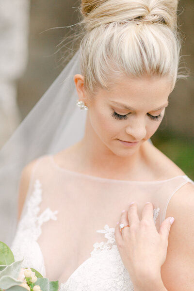 classy  bridal look with high bun and long veil while bride looks down at ring on hand
