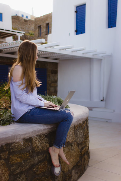 A female writer sits on a wall with a Mac laptop