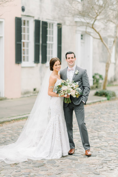 Charleston Bride in Hayley Paige Wedding Dress with Blush and Greenery Bouquet with Groom in Grey Suit with Pink Bow Tie
