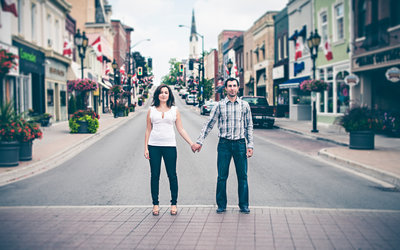 A beautiful couple holding hands in the middle of a deserted Old Newmarket  high street.