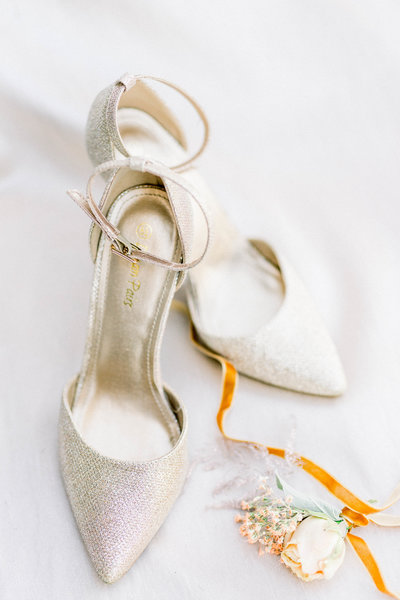 designer strappy bridal heels with groom's boutonniere wrapped in velvet