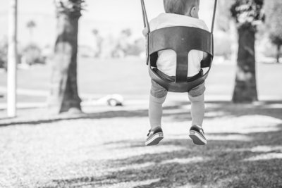 black and white photo of toddler feet in swing