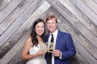 bride and groom holding a Mr & Mrs prop front of a wooden backdrop