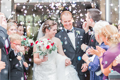 Bride and groom smile bright while leaving their wedding ceremony while being showered in bubbles by their guests