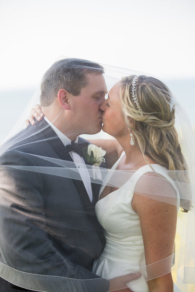 Erie, PA bride and groom kiss during portraits at Lawrence Park golf club