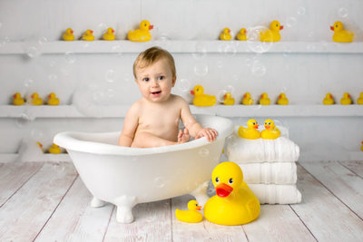 baby boy in white bathtub with rubber ducks