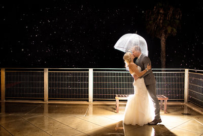 Bride and Groom kissing under clear umbrella in the rain at Museum of Contemporary Arts