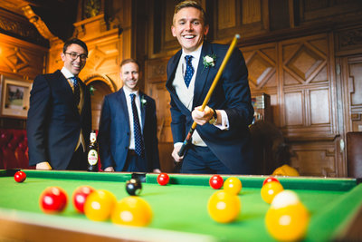 groom playing pool with best man at allerton castle
