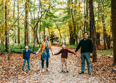 lifestyle photography of family holding hands in the woods at Wolf Trap Park